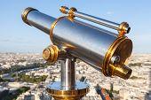 Shining Telescope Mounted On The Railings Of Eiffel Tower