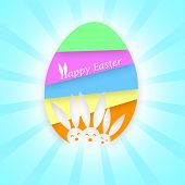 Three heads of Easter bunnies on a colorful Easter Egg on a light rays background