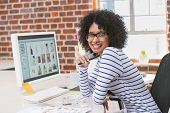 Portrait of smiling female photo editor sitting at office desk