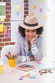 Portrait of smiling female interior designer sitting at office desk