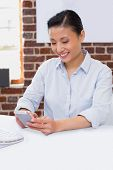 Smiling female executive text messaging in the office