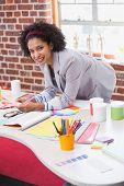 Portrait of female interior designer at office desk