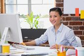 Portrait of smiling young woman working at office desk