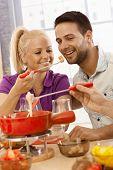Loving couple having cheese fondue, woman feeding man, smiling.