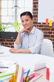 Portrait of smiling female executive sitting at office desk