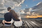 Asian young couple sit and hug together against the sky in outdoor.