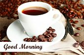 Cup of coffee and coffee beans with chocolate glaze on wooden background