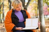 pregnant woman with blank photo album in autumn park