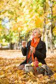 pregnant woman blow bubbles in autumn park