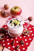 Oatmeal with yogurt in pitcher, apples and walnuts on polka dot napkin on pink wooden background