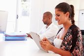 Woman Using Digital Tablet In Office Of Start Up Business