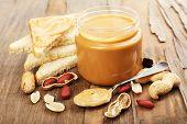 Creamy peanut butter in jar, on wooden table