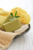 "picture of bath sponge  - Greek olive soap with bath towels and bath sponge in bowl closeup. The words on soap translates as ""best quality""