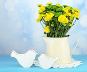 Yellow and green flowers in vase on wooden table, on light background