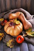 Pumpkins on sackcloth on wooden table on wooden wall background
