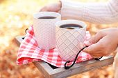 Woman holding tray with cups of tasty hot drink, close-up,  on autumn leaves background