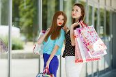 image of overspending  - Shopping and two beautiful women with shopping bags in a shopping center near the windows - JPG