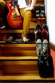 Person sitting beside Different shoes on a staircase and holding a guitar