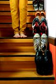 Person standing beside Different shoes on a staircase