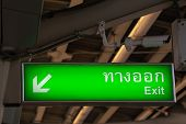lluminated green exit sign in Thai