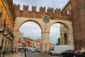 People And Vehicles Near The Medieval City Gates On Portoni Della Bra. Verona, Italy