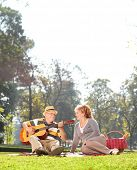 Senior playing guitar to his wife on a picnic in park seated on a blanket shot with a tilt and shift lens