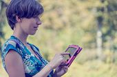 Young Woman Using A Pink Tablet Outdoors