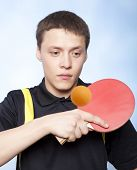stock photo of ping pong  - Young man playing ping pong against a blue background  - JPG