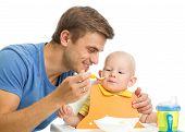 father feeding baby son by healthy food
