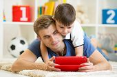 father and son kid play with tablet computer indoors