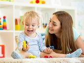 kid boy and mom playing with construction toys indoor