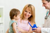foto of douche  - doctor counseling mother and boy about nasal irrigation or douche with neti pot - JPG