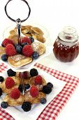 Poffertjes With Berries And Jelly On A Cake Stand