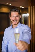 Handsome man holding flute of champagne at the bar