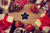 a pile of gifts and christmas ornaments, such as christmas balls and stars, on a rustic wooden table with a heart-shaped chalkboard with the text merry christmas in the center poster