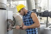 Young worker using wrench on industrial machine