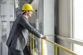 Side view of smiling male architect leaning on railing in industry
