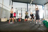 Group of young male and female athletes lifting kettlebells