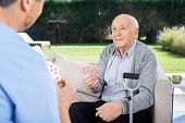 Male caretaker and senior man playing cards while sitting on couch at nursing home