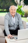 Portrait of happy senior man using laptop while sitting on couch at nursing home porch