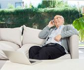 Relaxed senior man using mobile phone while sitting on couch at nursing home porch