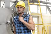 Young male worker with wrench leaning on large industrial valve