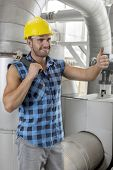 Happy young male worker gesturing thumbs up in industry