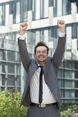 Portrait of cheerful businessman celebrating success outside office building