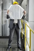 Full length of young male architect holding blueprint in front of face at industry