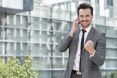 Portrait of successful young businessman using cell phone against office building
