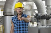 Portrait of confident young worker pointing at you in industry