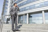 Full length businessman answering cell phone while standing on steps outside office