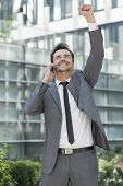 Excited young businessman using cell phone outside office
