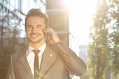 Portrait of smiling businessman using cell phone outdoors
